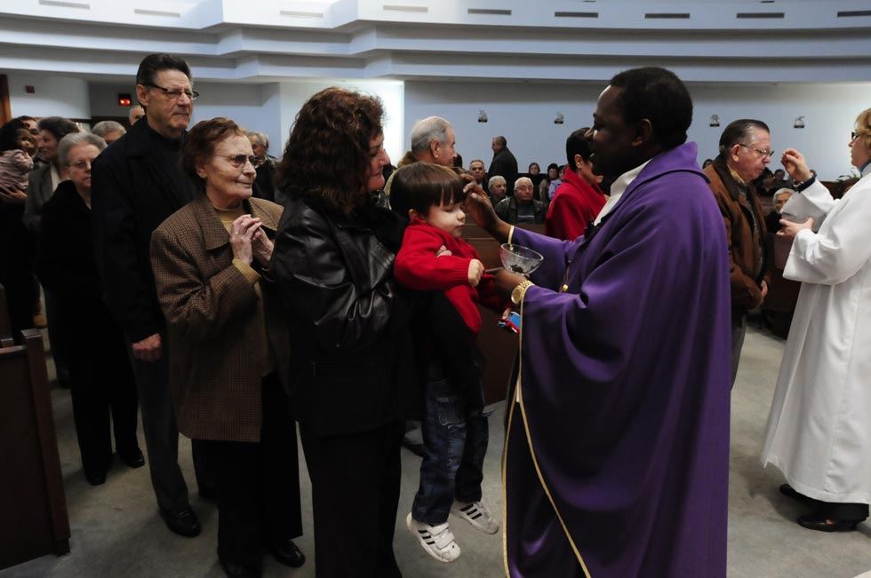 Father Antonio Jorge Tchingui blesses Zachary Gacome, 2, on the forehead with ashes during a noontime Ash Wednesday mass at Our Lady of Fatima Catholic Church in Hartford. Fr. Tchingui, the Portuguese-speaking pastor of Our Lady of Fatima.