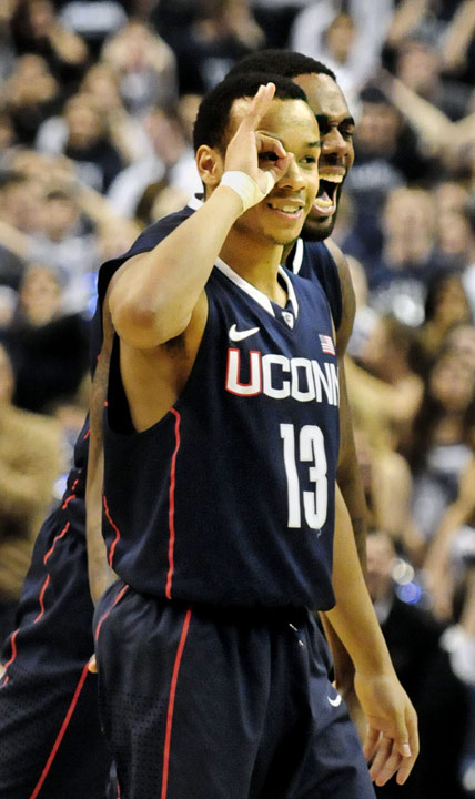 UConn's Shabazz Napier signals for three after making a buzzer-beater with less than a second left to lift the Huskies' 73-70 overtime win over Villanova at the Wells Fargo Arena in Philadelphia. Alex Oriakhi yells in celebration behind him.