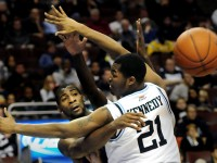 UConn&#039;s Andre Drummond passes around Villanova forward Markus Kennedy in the first half.