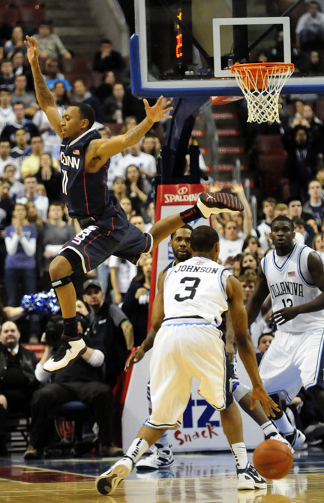 UConn's Ryan Boatright seems to make a flying leap over Villanova guard Tyrone Johnson.