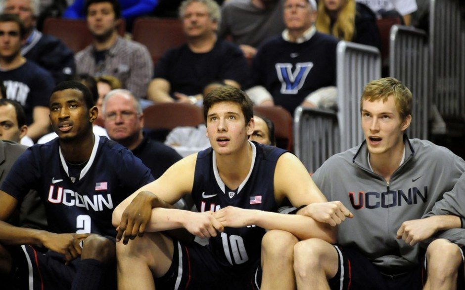 UConn's DeAndre Daniels, Tyler Olander and Niels Giffey sit with locked arms, holding their breath during free-throws in OT.