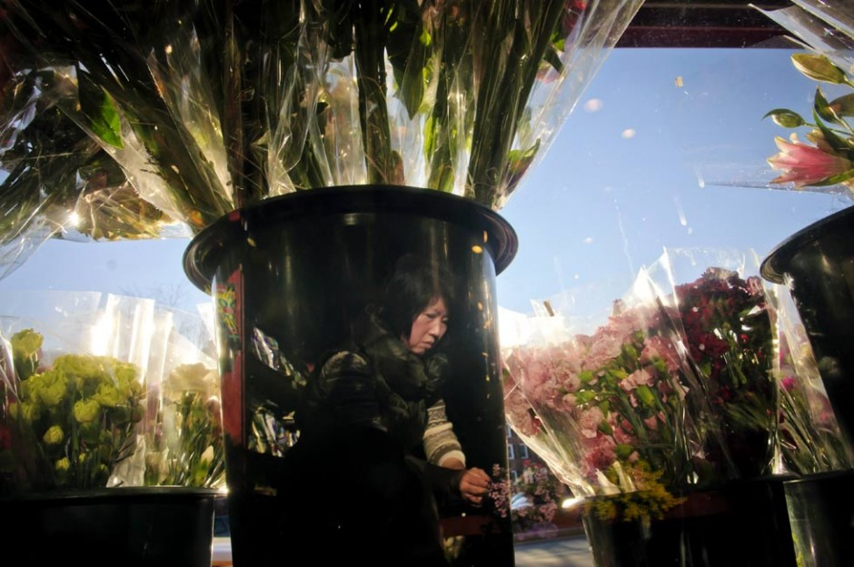 NEW HAVEN - 02.13.2012 - Reflected in a flower vase, Kelly Cho, the owner of Gourmet Heaven in New Haven, makes flower bouquets inside her store. Cho says she usually orders about 1000 flowers per week but doubles that for Valentine's Day. MARK MIRKO | mmirko@courant.com