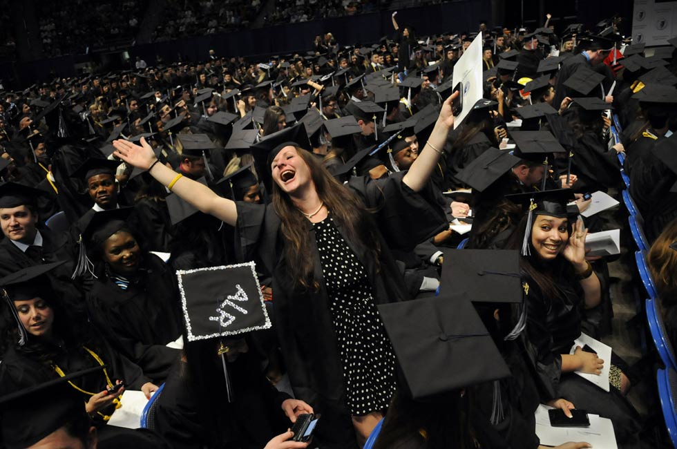 Arianna Thibodeau of Simsbury signals her parents in the upper level of the XL Center with an emotional thank-you at the start of the Central Connecticut State University commencement exercises Friday night. The arena was packed as the thousands of graduates waited to receive their degrees.