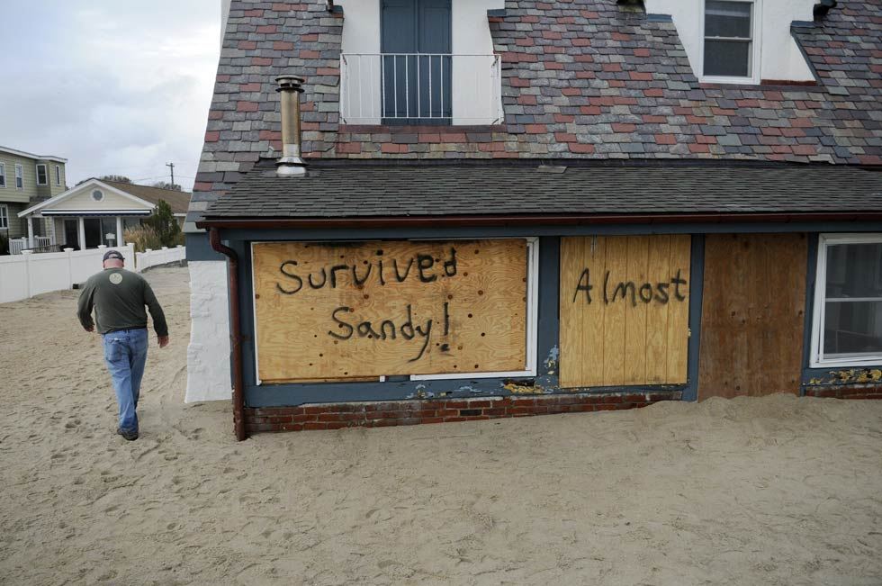 "Christopher Harding of Wethersfield walks around his family's beachfront home at White Sands Beach Tuesday. Although the house is intact, more than 6' of water traveled through the house and filled it with sand so it ""almost"" survived."