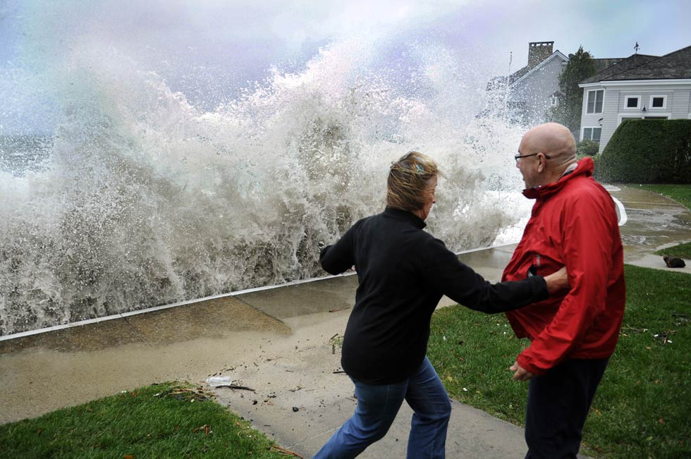 Nancy Grant and George Vinick leap out of the way of a huge wave in front of Grant's home in Neptune Park Monday. The water at 10 am was already breaching the seawall and both residents left their homes.