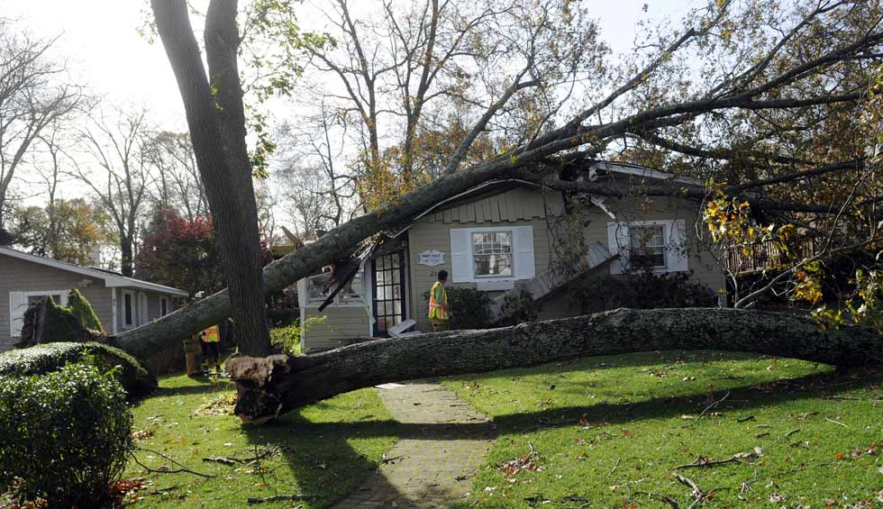 An Old Lyme firefighter checks the damage to this home on Sargent Rd. where a giant tree fell, crushing it Monday night.