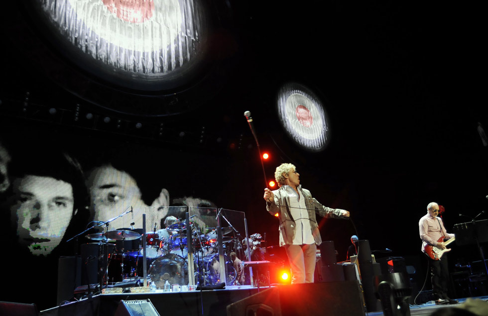Old black & white images of the Who from the 60's are displayed behind Daltrey and Townshend.