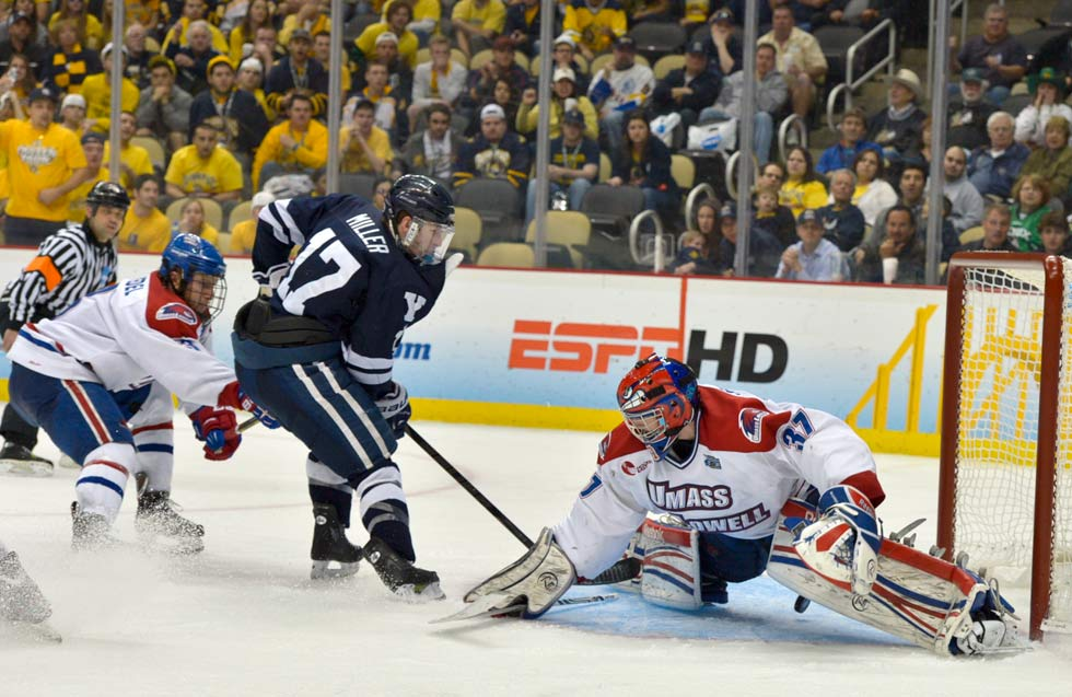 Andrew Miller scores in overtime for Yale against UMass-Lowell goalie Connor Hellebuyck to advance the Bulldogs to the Frozen Four final game against Quinnipiac at the Consol Energy Center in Pittsburgh.