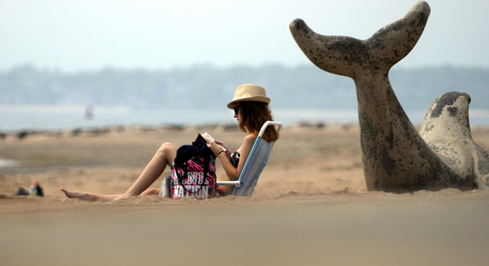 Jocelyn Thomas of East Haven took advantage of the hot and humid weather Thursday afternoon to work on her tan and spend some time on the beach at Lighthouse Point with her book and a seal. The weather over the holiday weekend is expected to turn decidedly colder with temps in the 40-50's. The beaches should be pretty empty Saturday and Sunday.
