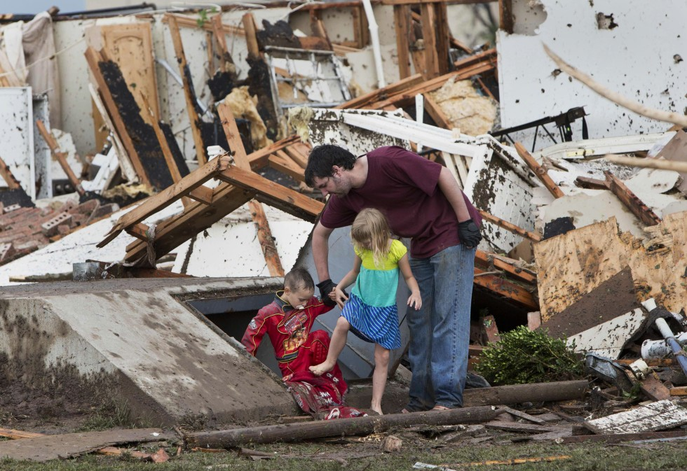 5/20/2013 -- A man and two children walk through debris after a huge tornado struck Moore, Oklahoma, near Oklahoma City, May 20, 2013. REUTERS/Richard Rowe