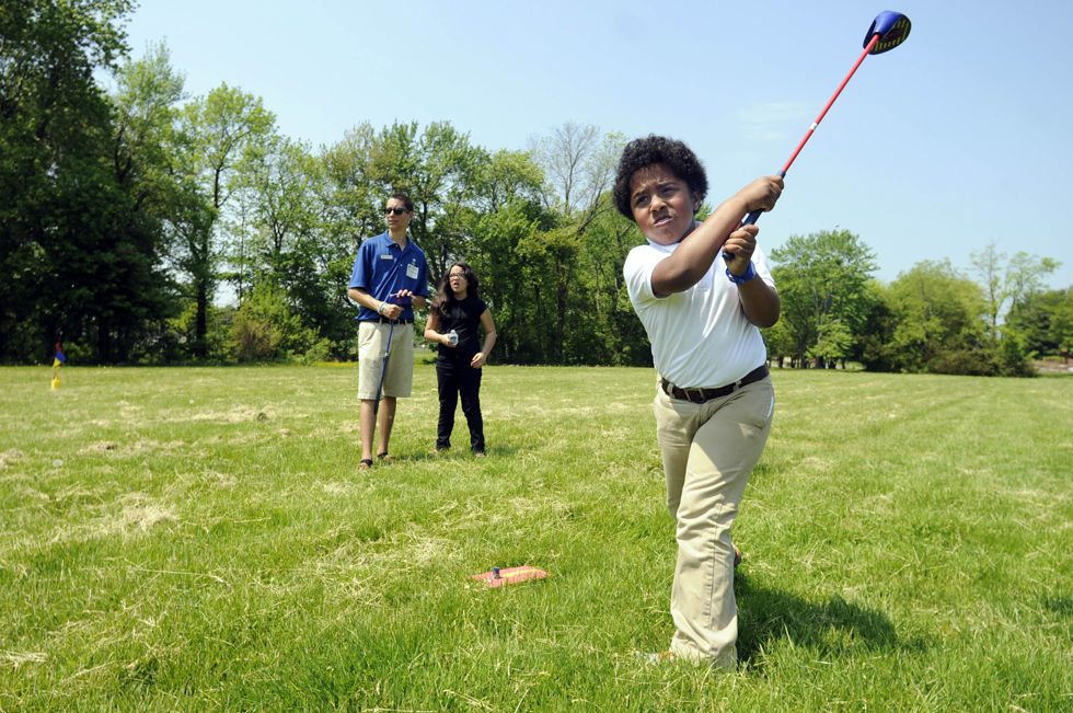 2013.05.21 - Bloomfield, CT - Sylvester McGovern (right) takes a shot during the SNAG (Starting New At Golf) program at Metacomet Elementary School Tuesday, while instructor Tom Burns, from Wintonbury Hills Golf Course, and classmate Diana Theriault, watch.