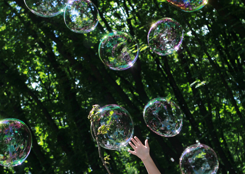 A child plays with soap bubbles at an event to support autistic children and their families in a park in Kiev, May 28, 2013. Autistic children and their families spent the day in the park with entertainment, clowns, and other family activities. REUTERS/Gleb Garanich