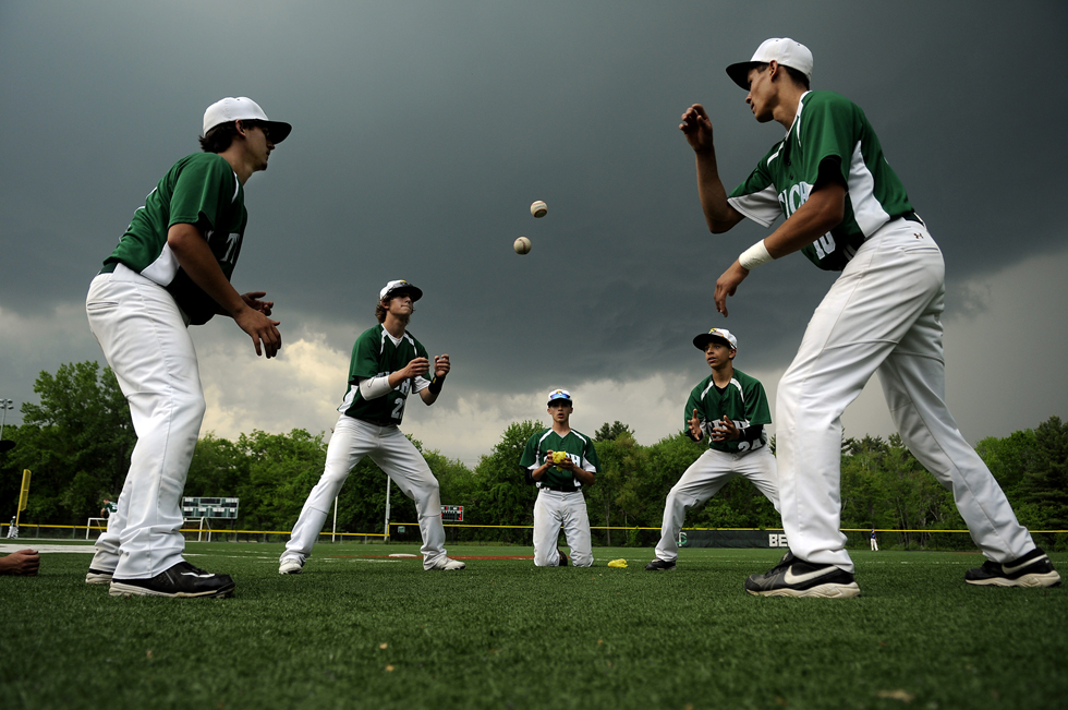 "2013.05.21 - Manchester, CT - (L to R)  Michael Musumeci, Ryan Davis, Steven Soto and Thomas Blays of Cheney Tech play a game of ""2 ball"" during a stoppage of play against Wilcox Tech due to lightening Tuesday afternoon in Manchester. The game was called due to heavy rain that followed the delay with Cheney leading 4-1 and Wilcox at bat in the top of the 5th inning. The game will be continued Wednesday afternoon.  Isiah Quiles (C) watches the action after being knocked out earlier in the game."