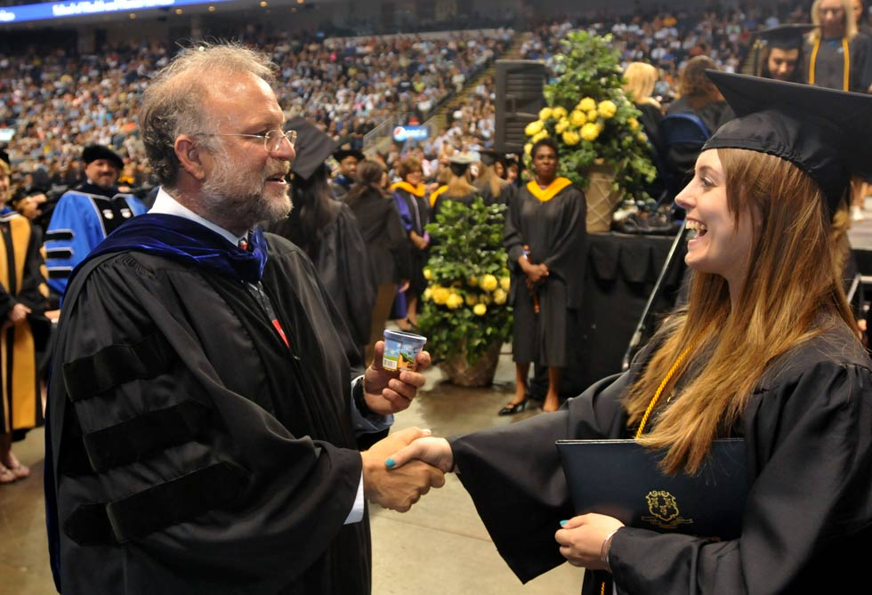 Jerry Greenfield, co-founder of Ben &amp; Jerry's ice cream gives graduates a samples of ice cream after they receive their diplomas at the Southern Connecticut State University at Webster Bank Arena Friday morning. 