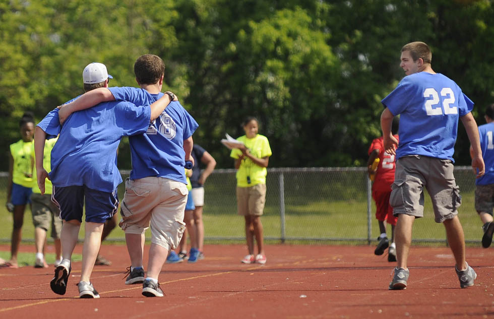 Two athletes from West Haven High School run together as they are cheered on by a partner (right) during the Southern Connecticut Conference Unified Sports track meet at West Haven High School Thursday, May 30, 2013. CLOE POISSON|cpoisson@courant.com