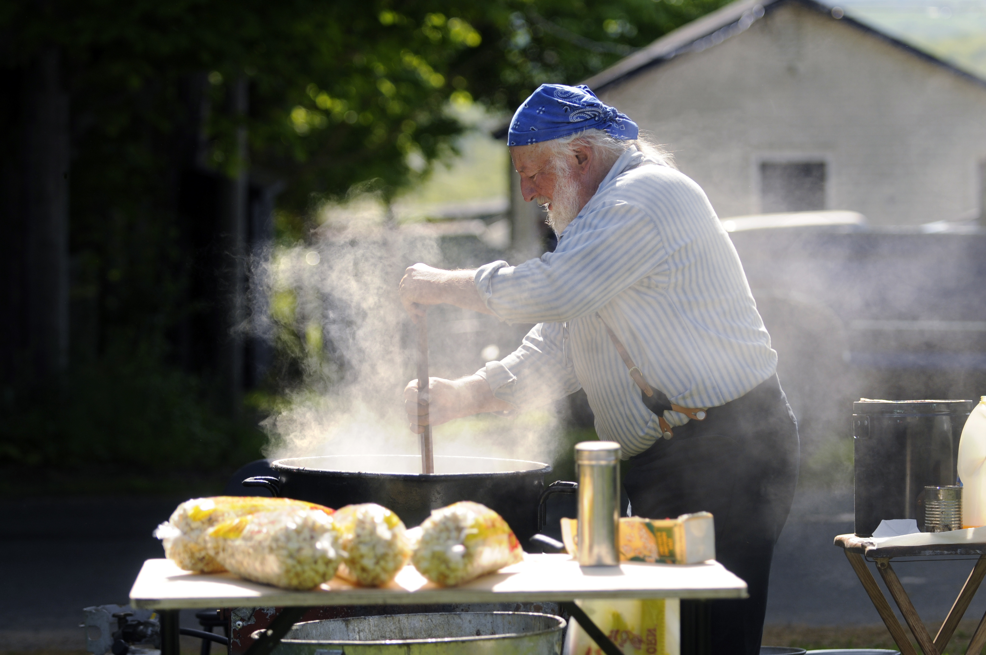 2013.05.16 - Durham, CT - Al Kostuk, of Durham, stirs a batch of kettle corn at the Durham Farmer's Market on the town green  Thursday.  Kostuk, a retired mechanic, is the proprietor of Pisgah Mountain Primitives and gives early American living history demonstrations, including open fire cooking and blacksmithing.  He cooks and sells the kettle corn at the market every Thursday afternoon.