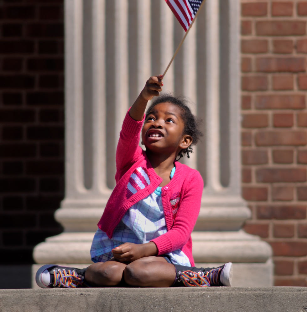 Deonnah Richburg, 6, of Manchester waves the U.S. flag atop her prime viewing spot along East Center Street at the Memorial Day parade in Manchester on Monday morning. The wet weather system moved out of the region to make way for a picture-perfect parade day.