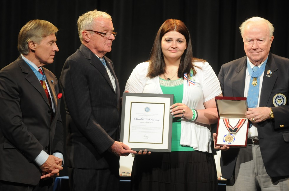 Hannah D'Avino, sister of behavioral therapist, Rachel D'Avino, accepts a certificate from Medal of Honor winners, from left, Paul W. Bucha, Thomas G. Kelley, and Bruce P. Crandall.