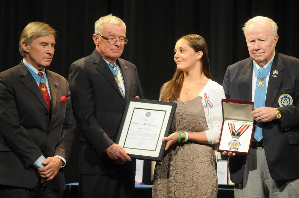 Erica Lafferty, daughter of school principal Dawn Hochsprung, accepts a certificate from Medal of Honor winners, from left, Paul W. Bucha, Thomas G. Kelley, and Bruce P. Crandall.