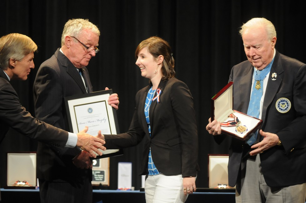 Kelly Murphy , daughter of paraeducator Anne Marie Murphy,  accepts a certificate from Medal of Honor winners, from left, Paul W. Bucha, Thomas G. Kelley, and Bruce P. Crandall.