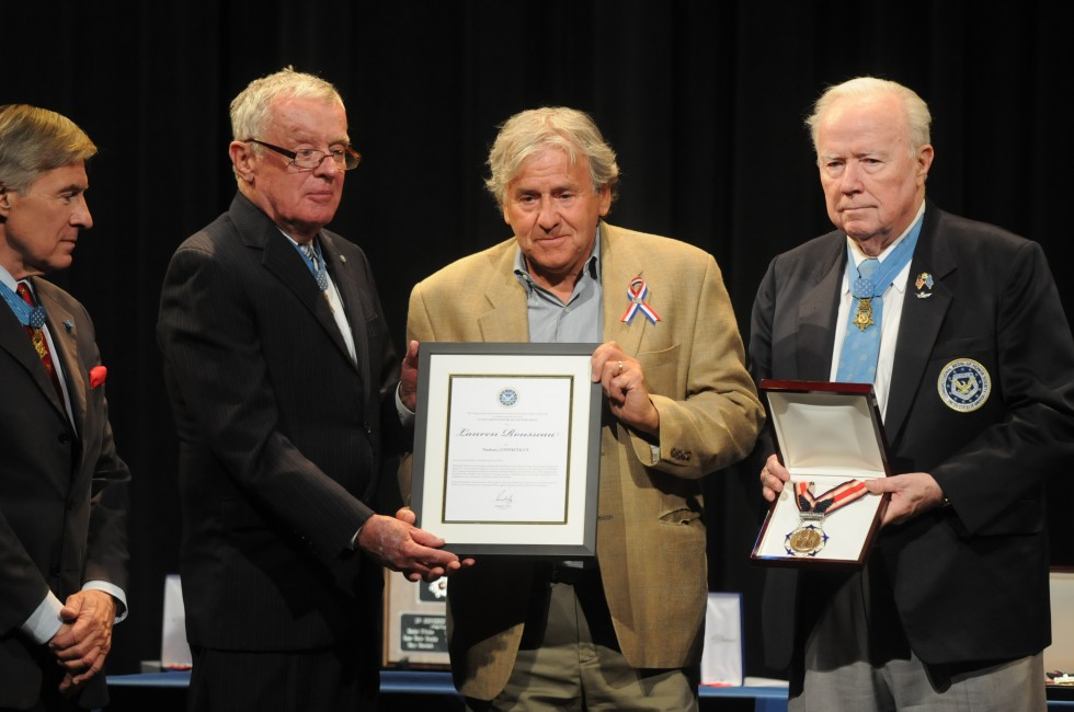 Gilles Rousseau, father of substitute teacher Lauren Rousseau, accepts a certificate from Medal of Honor winners, from left, Paul W. Bucha, Thomas G. Kelley, and Bruce P. Crandall.