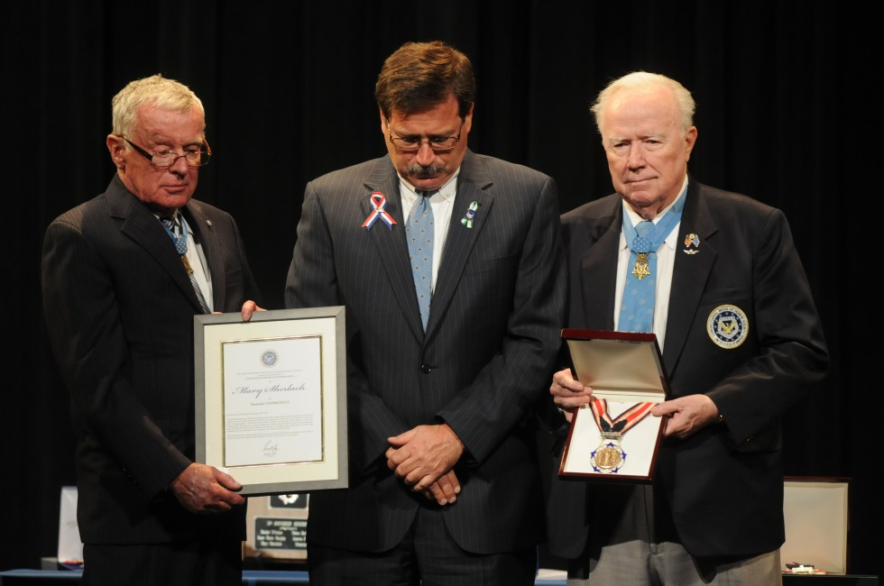 William Sherlach, husband of school psychologist Mary Sherlach, aaccepts a certificate from Medal of Honor winners, from left, Thomas G. Kelley, and Bruce P. Crandall.
