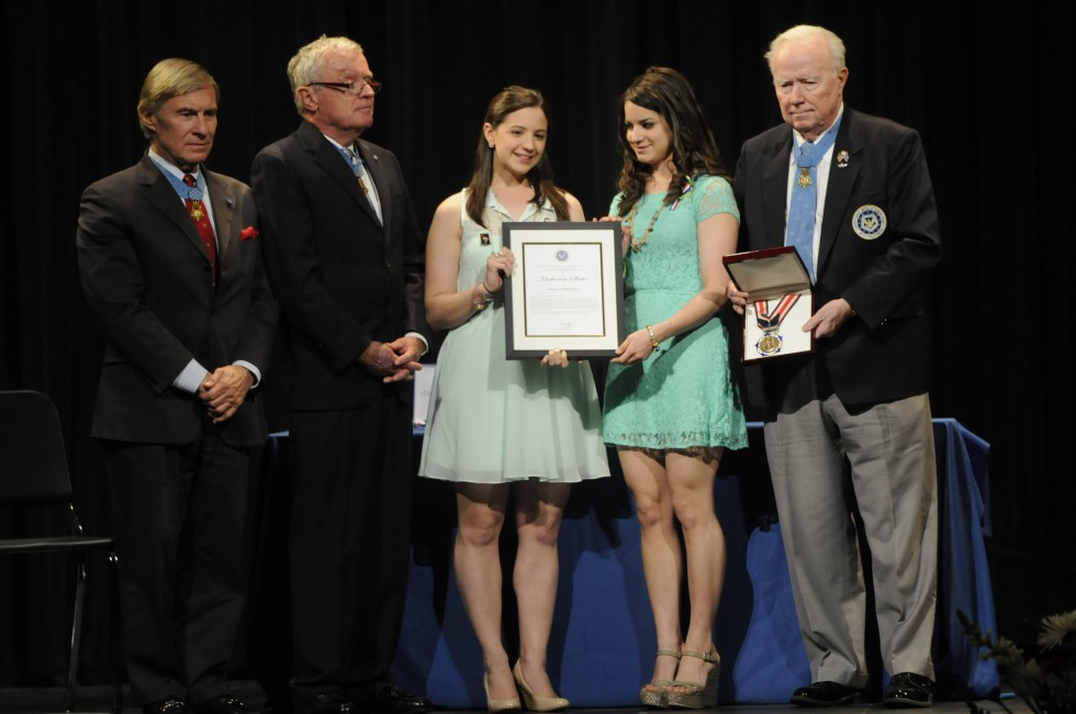 Jillian Soto, left, and Carlee Soto, sisters of slain teacher Victoria Soto, accept a certificate from Medal of Honor winners, from left, Paul W. Bucha, Thomas G. Kelley, and Bruce P. Crandall.