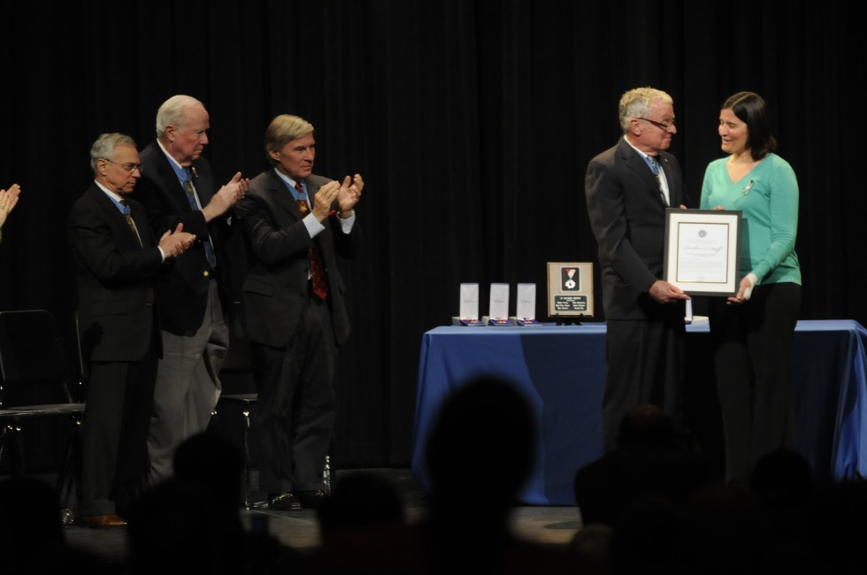 Natalie Hammond, a teacher and survivor of the Sandy Hook School shootings, who was shot in the foot, leg and hand, accepts the Citizen Honors Certificate of Commendation from Medal of Honors recipients, from left; Jack H. Jacobs, Bruce P. Crandall, Paul W. Bucha, and Thomas G. Kelley.