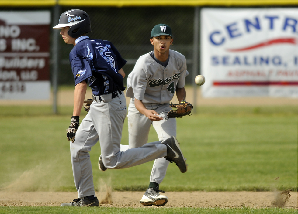 2013.05.17 - Manchester, CT - Stalys Delso Santos charges a ground ball as Omar Montalvo of East Catholic heads to thirdbase during the first inning but even routine plays turn into...