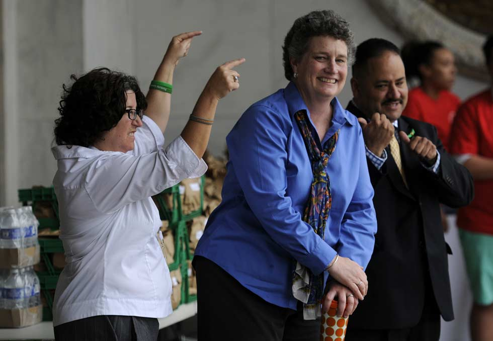 State Senator Beth Bye, center, takes a bow, pointed out by Vickie Veltri, State Healthcare Advocate and Senator Andres Ayala during a rally outside the State Capitol marking AIDS Awareness Day.