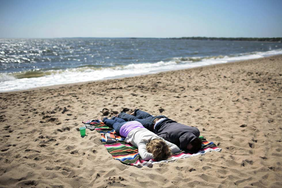 Courtney DeMaria and Will Cayer stay close to the sand where they say its not so bad as a stiff wind and cool temperatures kept many away from Hammonasset State Park beach on Memorial Day. DeMaria and Cayer are from New Haven.
