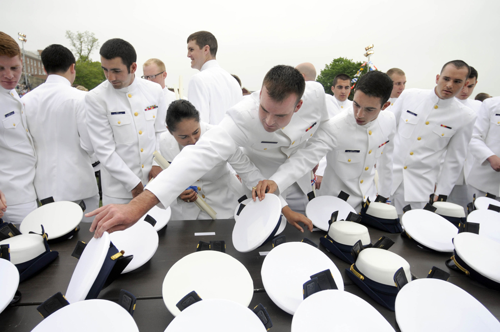 2013.05.22 - New London, CT - Newly commissioned officers look for their ensign hats at the U.S. Coast Guard Academy's 132nd commencement.