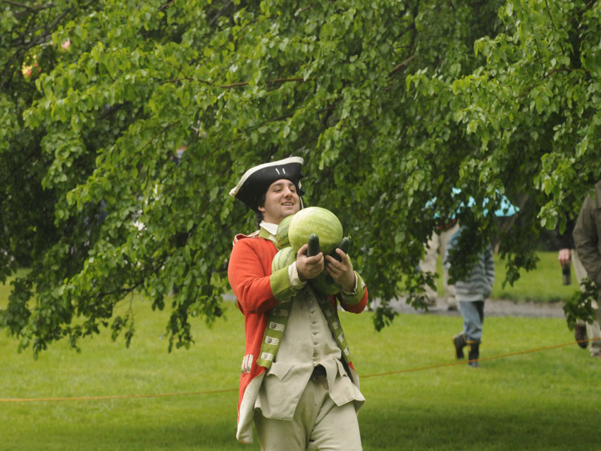-Anthony Riccio brings the melons to be sliced by Dave Loda on horseback at the Webb-Dean-Stevens Revolutionary War Encampment Saturday in Old Wethersfield.