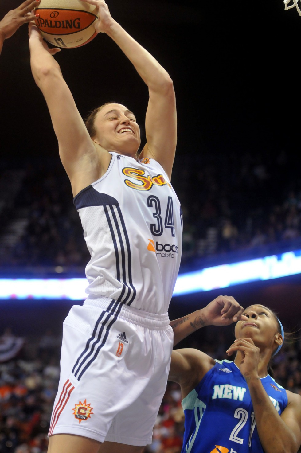 Connecticut Sun rookie Kelly Faris crashes the boards during the Sun season opener at Mohegan Sun Arena Saturday night.  Looking on is New York Liberty's Alex Montgomery. Connecticut Sun forward Mistie Bass, Kelly Faris and New York Liberty's Cappie Pondexter in action at the Sun season opener at Mohegan Sun Arena Saturday night. Photo by BRAD HORRIGAN | bhorrigan@courant.com