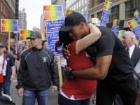 NBA player Jason Collins pauses to hug a woman as he marches during the Gay Pride Parade in Boston, Massachusetts June 8, 2013. REUTERS/Jessica Rinaldi