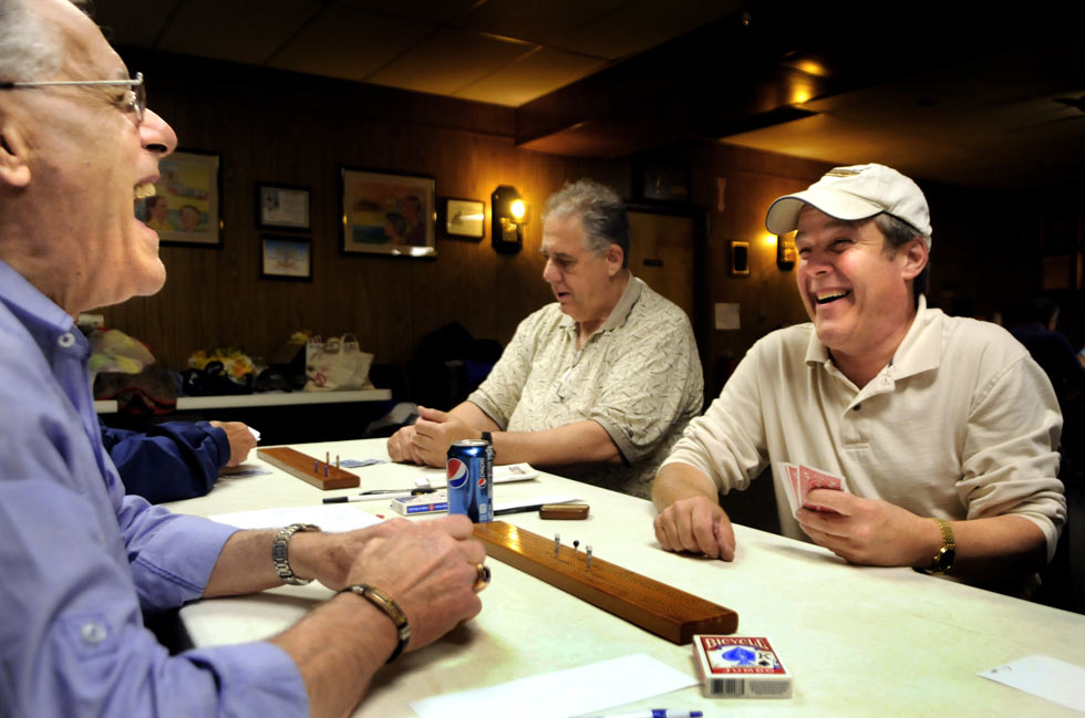 "Karl Russo of East Glastonbury, left, and Phil Martin of Newington, right, share a laugh over a hand of cribbage during the weekly meeting of the Hartford Metro Cribbage Club. More than 30 members meet on Monday nights at the Moose Lodge for some competitive games. ""This is the best two-handed game ever invented,"" said Martin."