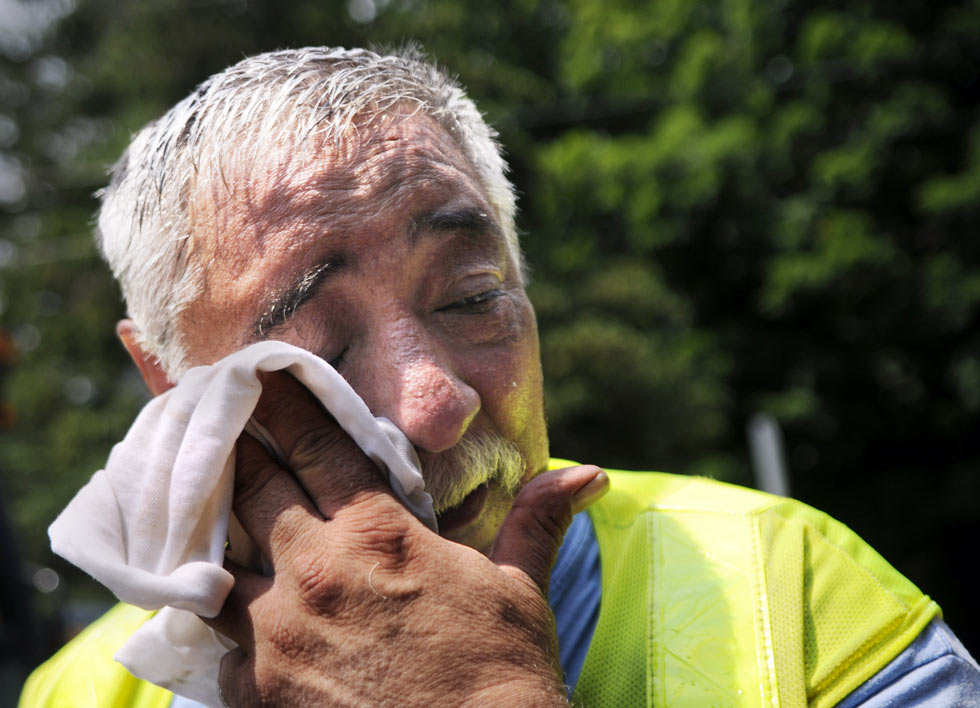 "With temperatures in the mid-90's and the air thick with humidity, Ron Ragion of Enfield, a Ct. Natural Gas Chief distribution fitter, wipes away the sweat as he finishes up installing a new plastic main line tie-in along Porter St. in Manchester Tuesday afternoon. ""This heat tears me up, "" he said as he climbed out of the trench where he was working. STEPHEN DUNN