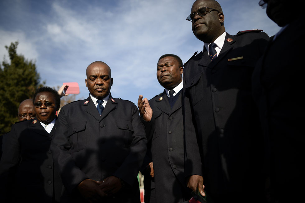 Members of the Salvation Army pray outside the Medi-Clinic Heart Hospital where former South African President Nelson Mandela is being treated, June 27, 2013. South Africans prepared to say farewell to ailing anti-apartheid leader Mandela, after his condition deteriorated, forcing President Jacob Zuma to cancel a trip to neighboring Mozambique. REUTERS/Dylan Martinez