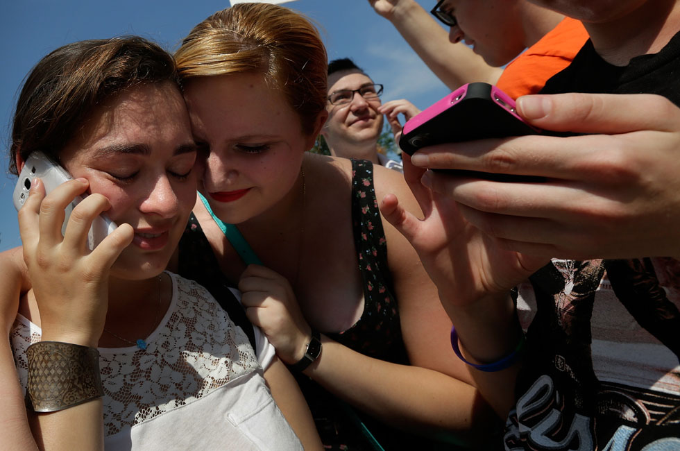 Elana Kessler (L) is embraced by friend Hannah Greenberg (R) as she speaks with her mother on the phone, on the steps of the US Supreme Court, while learning of favorable rulings issued by the court on same sex marriage cases, June 26, 2013. The high court ruled to strike down DOMA and determined the California's proposition 8 ban on same-sex marriage was not properly before them, declining to overturn the lower court's striking down of the law.  (Photo by Win McNamee/Getty Images)