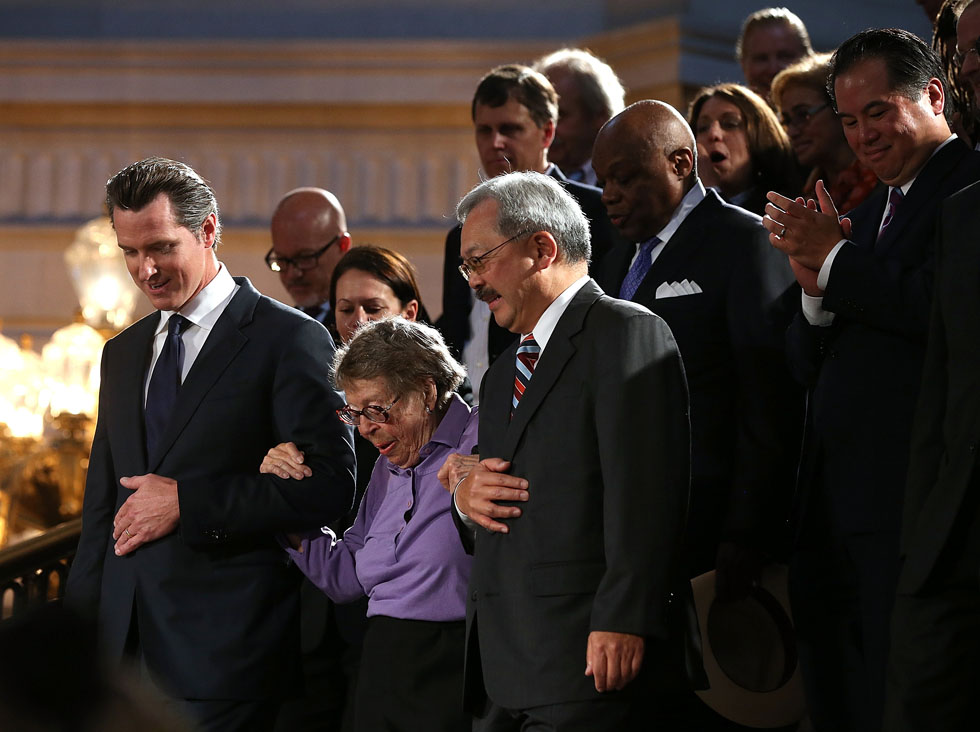 Phyllis Lyon (C), half of the first same-sex couple to be married in San Francisco's 2008 gay marriages, is escorted by California Lt. Gov Gavin Newsom (L) and San Francisco mayor Ed Lee during a rally after hearing results from the U.S. Supreme Court's rulings on gay marriage in City Hall June 26, 2013 in San Francisco. Lyon was widowed two months after she married Del Martin. (Photo by Justin Sullivan/Getty Images)