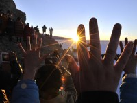 People raise their hands during a ritual at sunrise to celebrate the Aymara New Year on June 21, 2013, at the Uyuni salt flat in Bolivia. A crowd gathered to receive the first rays of Tata Inti (god Sun) during the celebration of the winter solstice that marks the beginning of the 5521st year in the Aymara calendar. AFP/PHOTO/Aizar RALDES/AFP/Getty Images