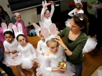 "Rosi Docal, a ballet instructor at Hartt, adjusts the ears of Megan Gill, 8, of West Hartford, one of the many bunnies in the Hartt School of Music Community Division's production of ""Snow White."" STEPHEN DUNN