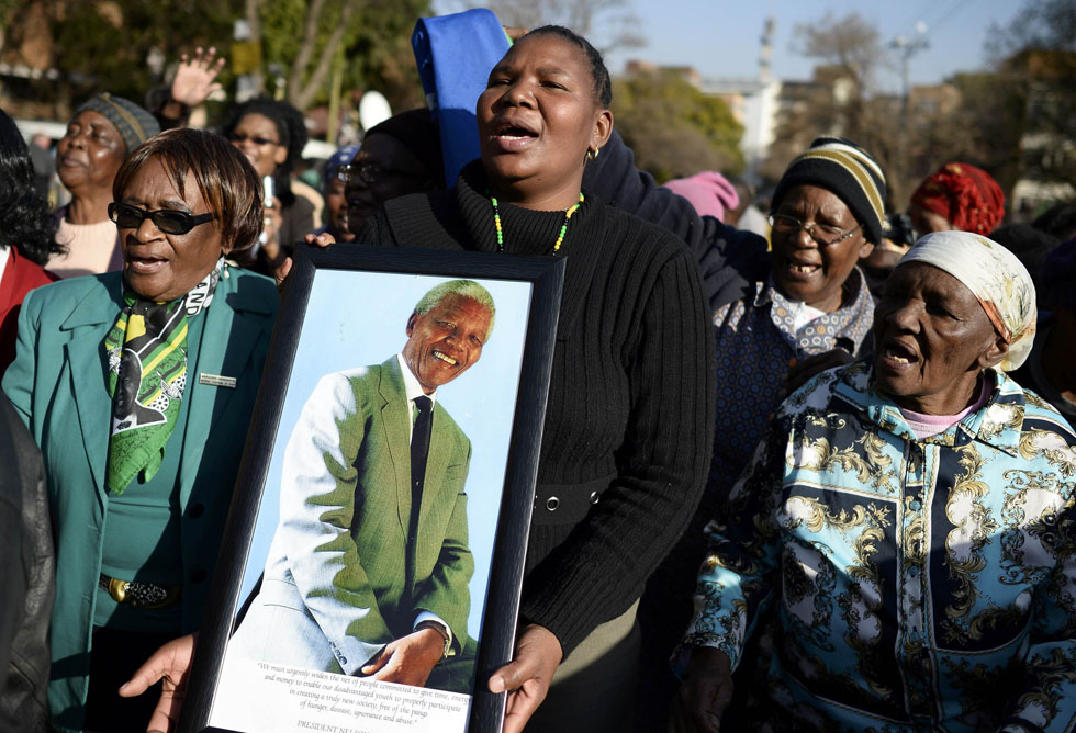 Well-wishers pay respect to ailing former South African President Nelson Mandela outside the Heart Hospital where he is being treated in Pretoria, June 27, 2013.    REUTERS/Dylan Martinez