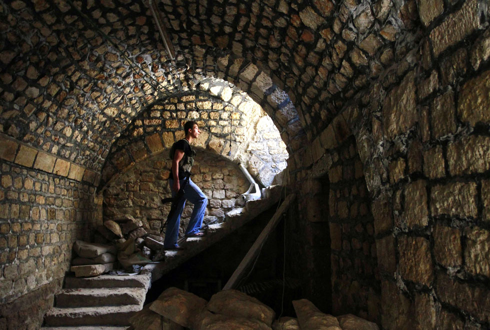 A Free Syrian Army fighter climbs the stairs, with his weapon, in the Bab al-Nasr neighborhood of Aleppo, Syria, June 28, 2013. REUTERS/Hamid Khatib