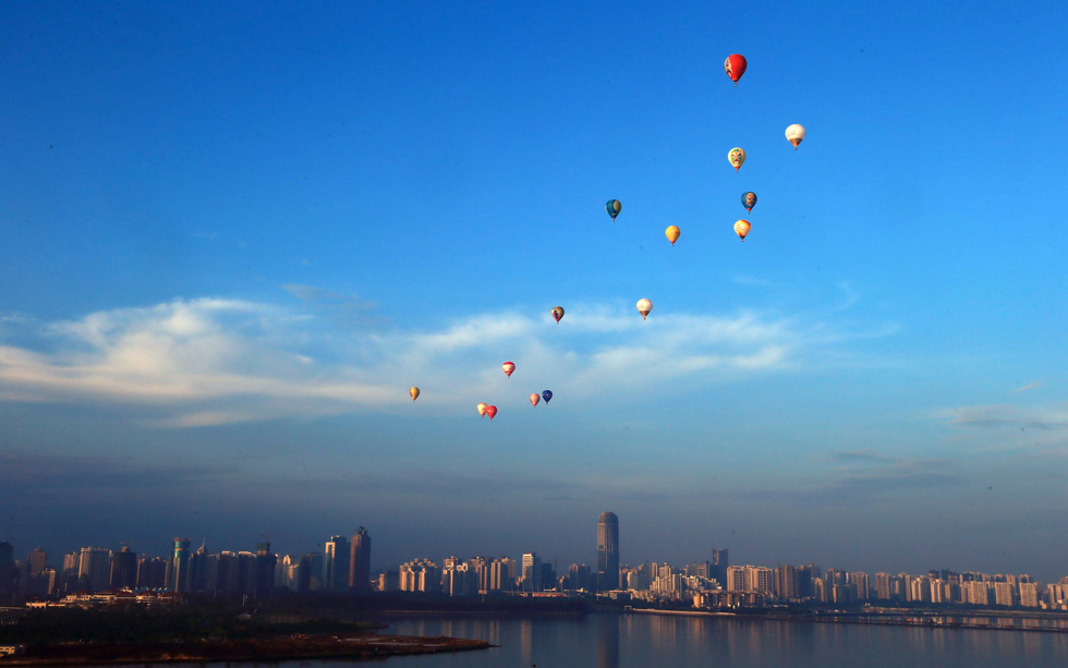 Hot air balloons fly across Qiongzhou Strait in Haikou, south China's Hainan province, during the H1 China Hot Air Balloon Challenge, June 18, 2013. Fifteen balloons flew over the strait in 2.5 hours and succeeded in landing on Leizhou Peninsula in Hainan. AFP/Getty Images