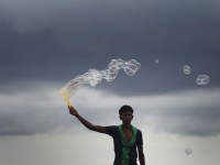 A street vendor blows bubbles for customers at Galle Face Green before the rain during the monsoon season in Colombo, Sri Lanka, June 28, 2013. REUTERS/Dinuka Liyanawatte