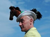 A man wearing a hat decorated with a miniature soft toy horse poses for photographs on the fourth day of the horse racing festival at Royal Ascot in Berkshire, west of London, on June 21, 2013. AFP PHOTO/CARL COURT/AFP/Getty Images