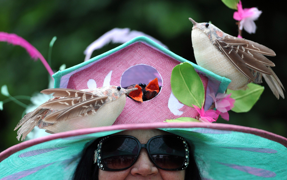 A woman poses for a photograph during the third day of Royal Ascot, in Berkshire, west of London, on June 20, 2013. AFP PHOTO/CARL COURT/AFP/Getty Images