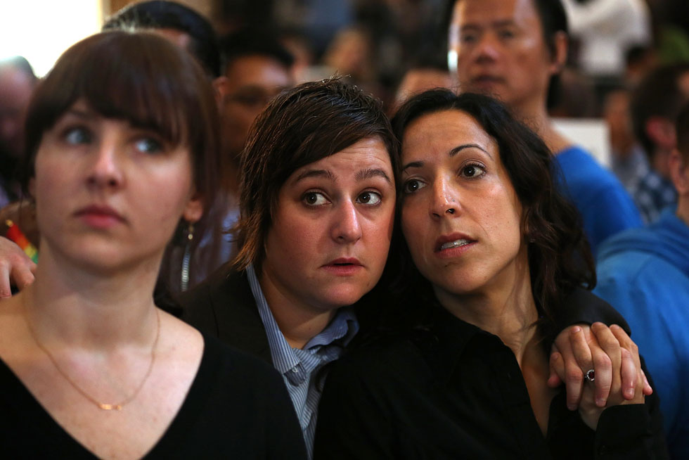 Same-sex couple Lori Bilella (C) and Renara Moreira (R) await results from the U.S. Supreme Court's ruling on gay marriage at San Francisco City Hall ,June 26, 2013. The high court struck down the Defense of Marriage Act (DOMA) and ruled that supporters of California's ban on gay marriage, Proposition 8, could not defend it before the Supreme Court. (Photo by Justin Sullivan/Getty Images)