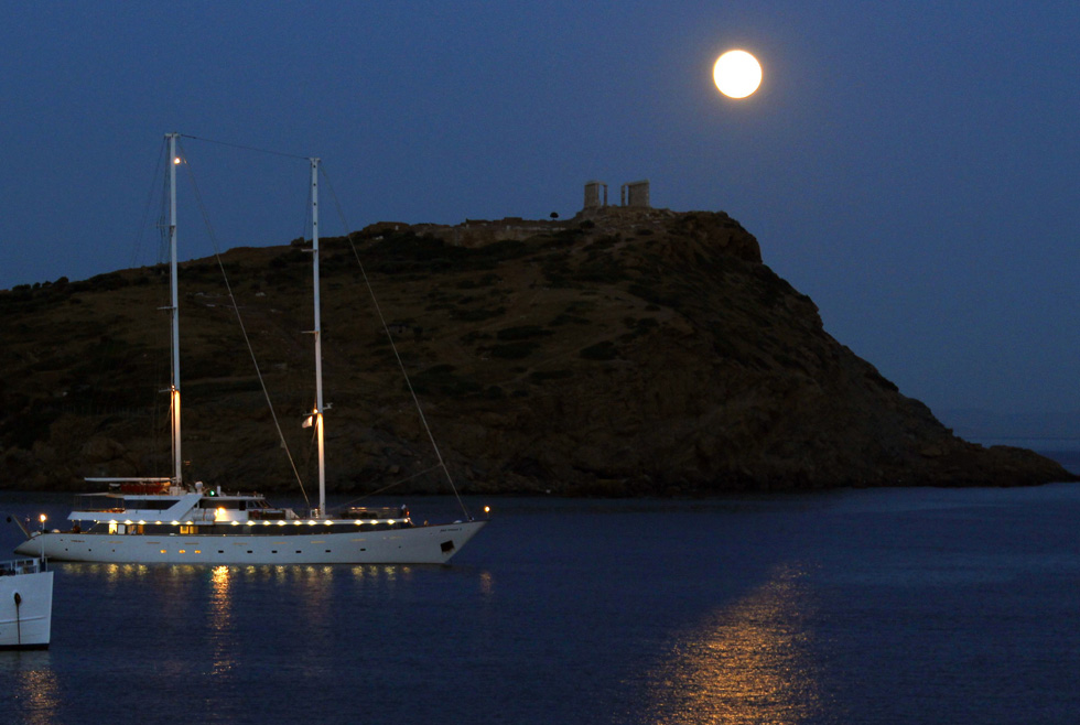 A supermoon rises over the temple of Poseidon, the ancient Greek god of the seas, in Cape Sounion in Greece, June 23, 2013. A perigee moon coincides with a full moon, creating a Supermoon when it passes by the earth at its closest point this year  REUTERS/Yannis Behrakis